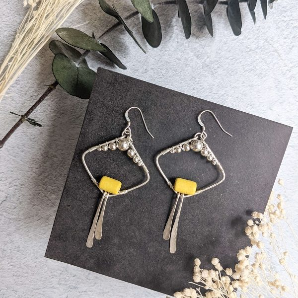 Boucles d'oreille MACA en argent, en partie recyclé et perle jaune en céramique.